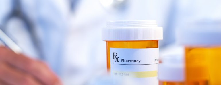 Doctor with RX prescription drug bottle selective focus
